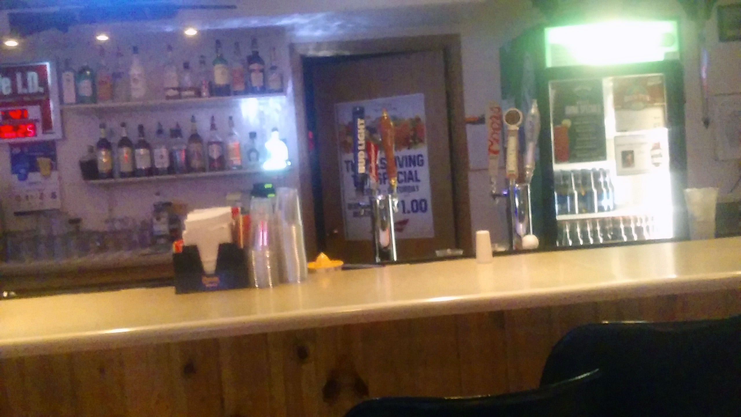 A picture of the main portion of the Eagles Bar, featuring the cash register with liquor bottles above, straws, napkins, and cups on the bar; and the beer bottle cooler to the right.