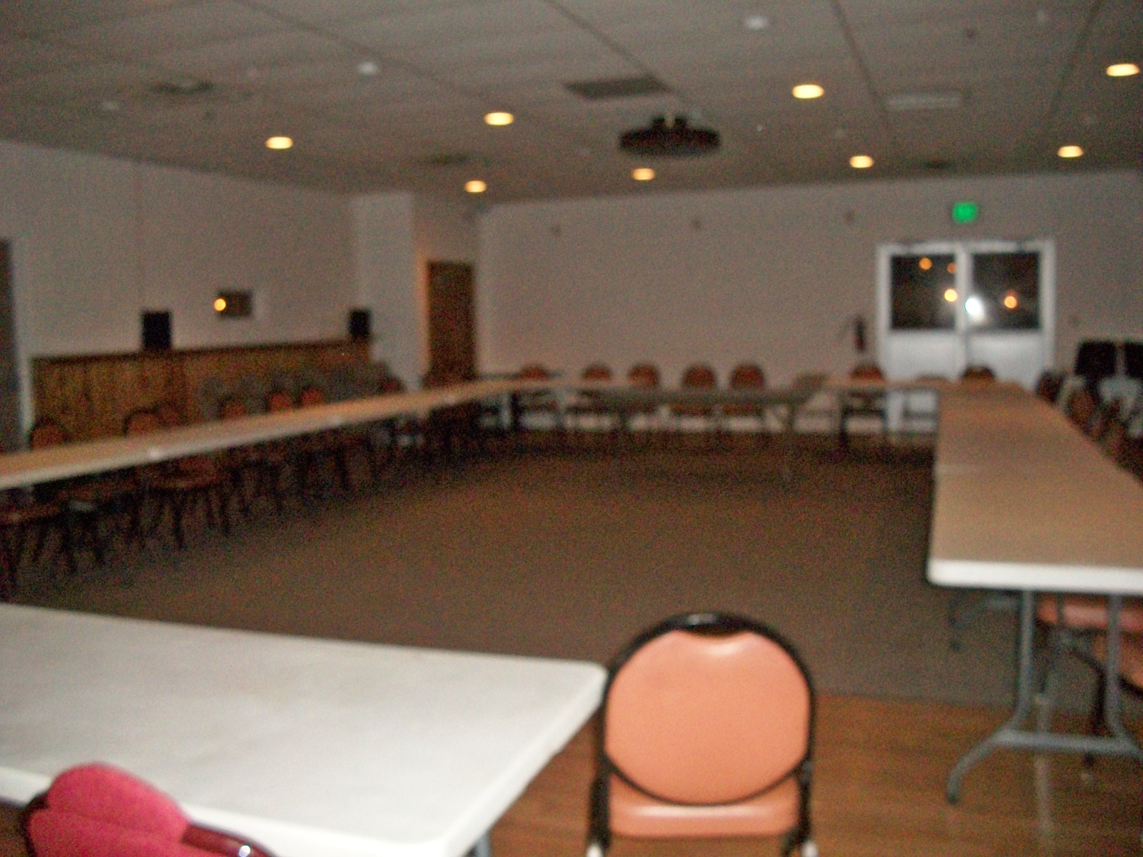 A picture of the large banquet room with its tables arranged in a large square for meetings. The room's primary entrance is in the background.