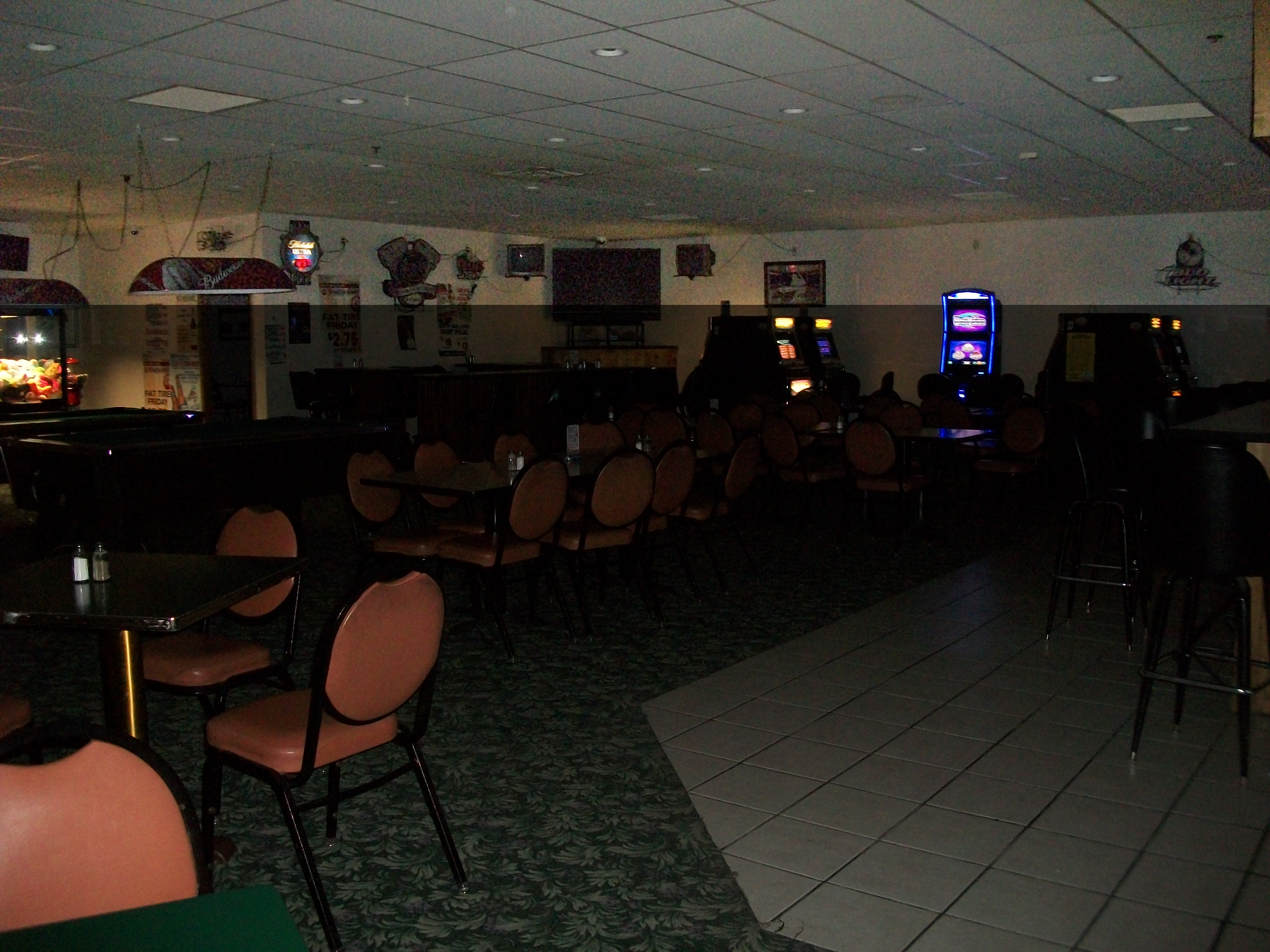 A picture of the main bar area taken from behind a pool table. In front of the two pool tables are tables and chairs, and to the sides are taller black barettes with bar stools beside them. There are video lottery machines beside some of the barettes on either side of the room. The bar is on the opposite side of the room.